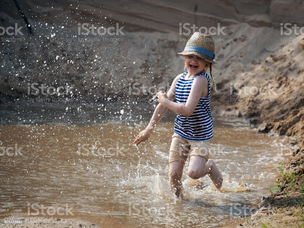 Incredibly happy child running fast on the water. Sand pit, muddy water in a puddle, much of the spill stock photo