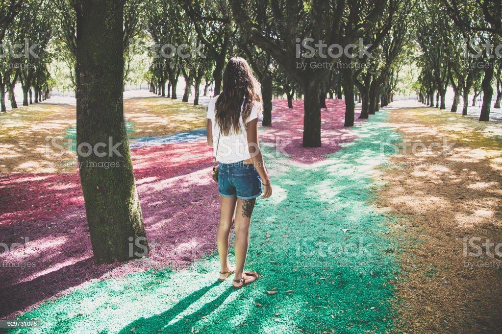 Indecisione, ragazza en ONU Giardino colorato con sassi arcobaleno - foto de stock
