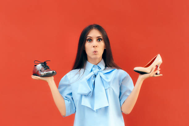 indecisive fashion woman choosing between flats and high heels shoes - flat shoe stock photos and pictures