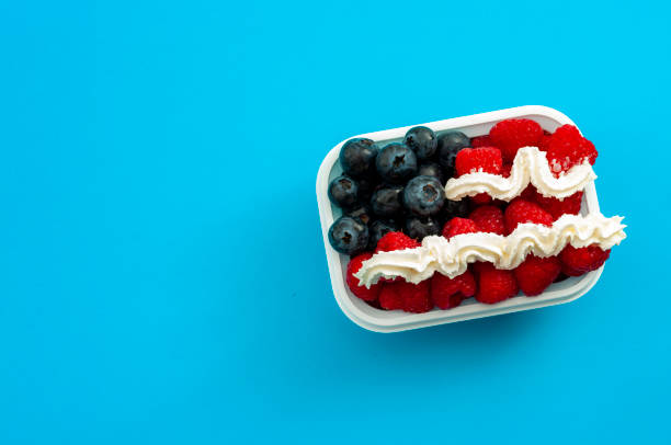 Independence day, happy fourth of july and sweet dessert concept theme with the american flag made of raspberries, blueberries and whipped cream, isolated on minimalist blue background with copyspace stock photo
