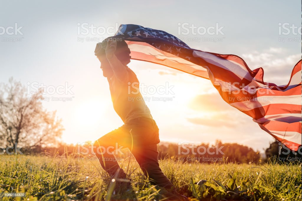 Independence day Little boy running with American flag at sunset 2018 Stock Photo