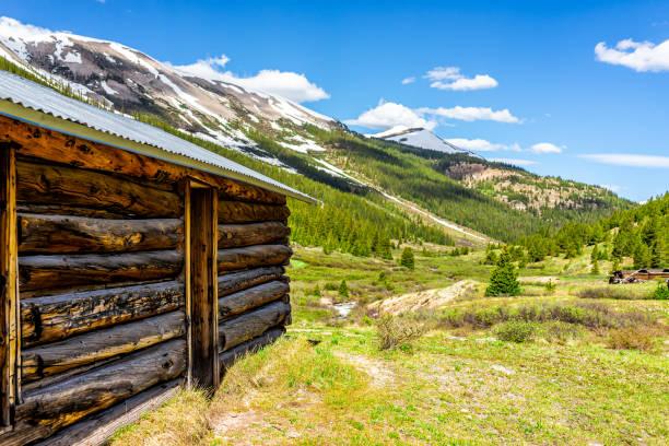 bağımsızlık pass yeşil çam ağaçları ve kar dağ zirveleri ile colorado white river ulusal ormanı'nda madencilik townsite ahşap kabin - independence day stok fotoğraflar ve resimler