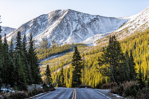 Independence Pass snow rocky mountain view and paved road scenic byway in morning sunrise near Aspen, Colorado in green autumn winter