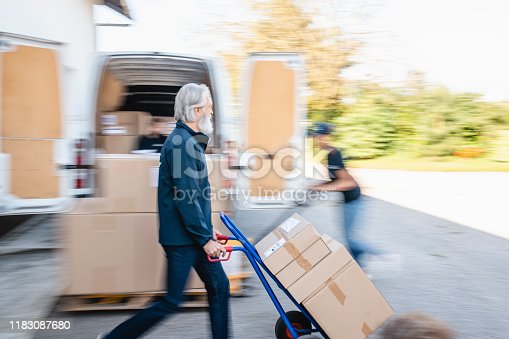 Blurred motion of mature independent gig delivery driver pushing hand truck and young woman pushing pallet jack of packages for transport.