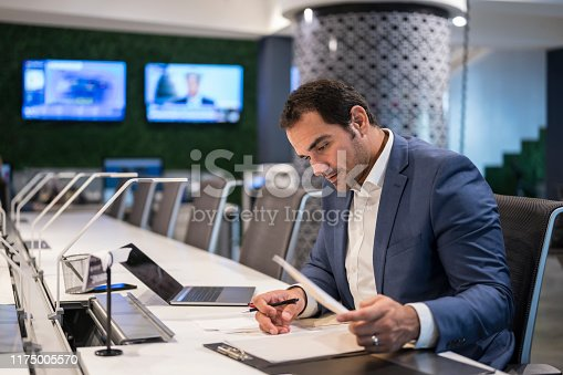 Dedicated Hispanic businessman in mid 30s sitting alone at desk after hours and making notes for a new project.