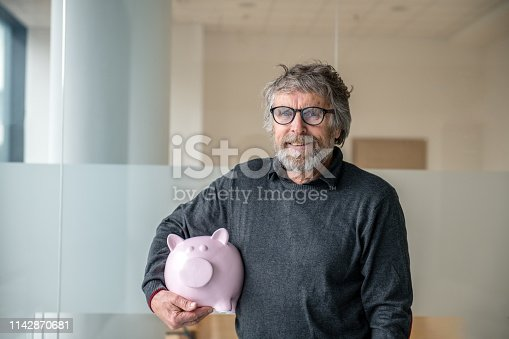 929887844 istock photo Independent Senior Man holding Piggy Bank. Save money and financial investment 1142870681