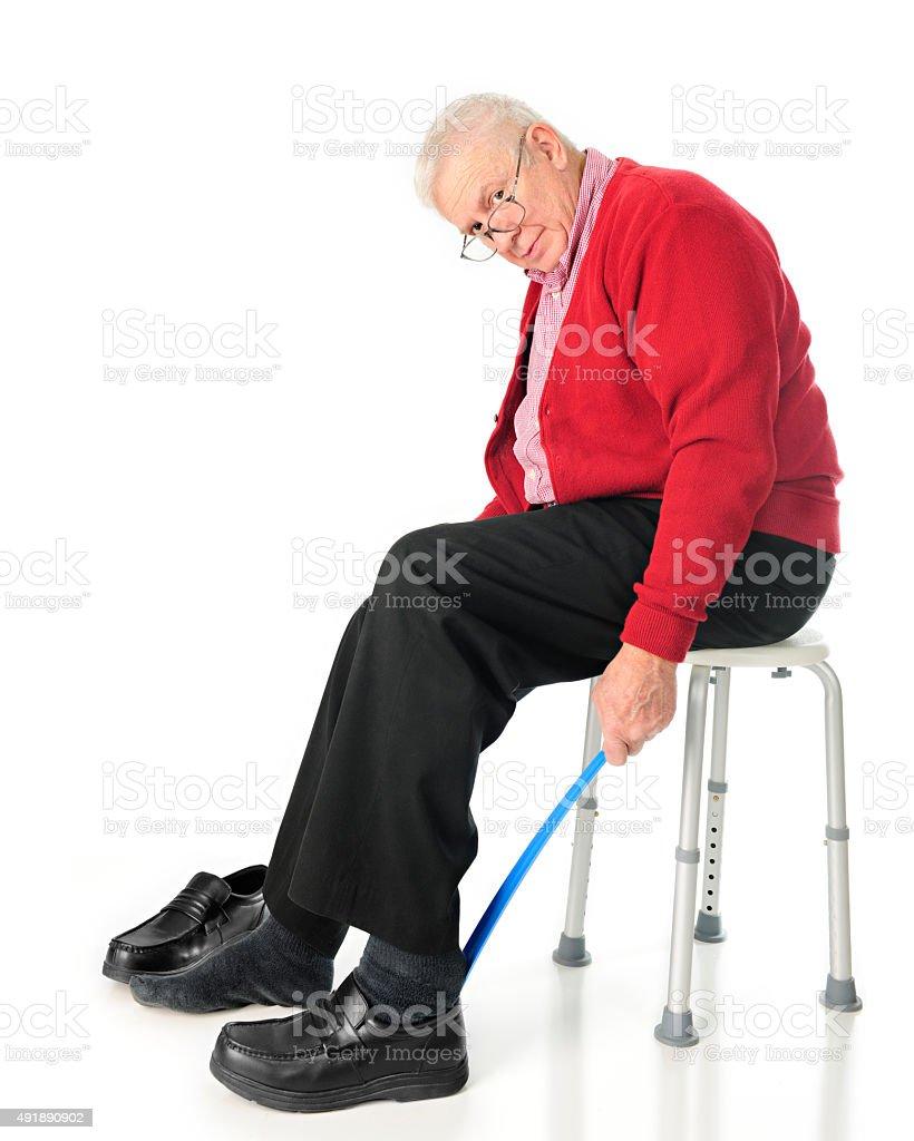 Independent Senior Using Assistive Dressing Device stock photo