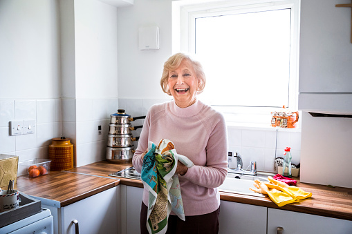 Senior woman looking happy as she stands in her kitchen drying dishes.