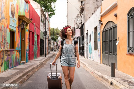 A young woman traveling through Buenos Aires with a backpack and wheeled luggage.