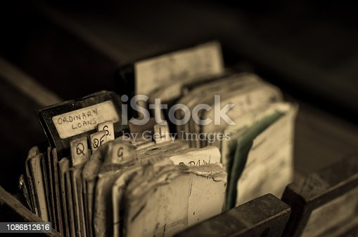 Index cards and borrowing slips in the drawer of an abandoned library card catalogue cabinet.  Selective focus.  Belfast, Northern Ireland.