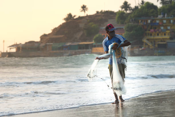 04/03/2020 India, GOA, Arambol, fisherman nets fish on the seashore in a protective mask so as not to spread the COVID-19 coronavirus during 21 day quarantine in India, concept of lockdown and curfew stock photo