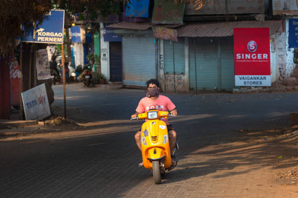 04/04/2020 India, GOA, Arambol, local people riding scooters in an empty city in protective masks during 21 day quarantine and full lockdown and curfew in India stock photo