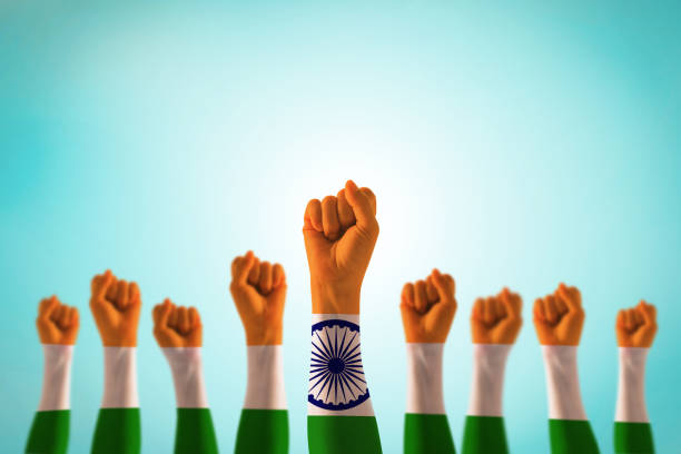 india national flag pattern on leader's fist isolated (clipping path) on blue mint sky for human equal rights, labor day concept - independence stock photos and pictures