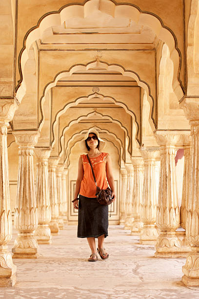 India, Rajasthan, Amber Fort, woman walking through archways in palace stock photo