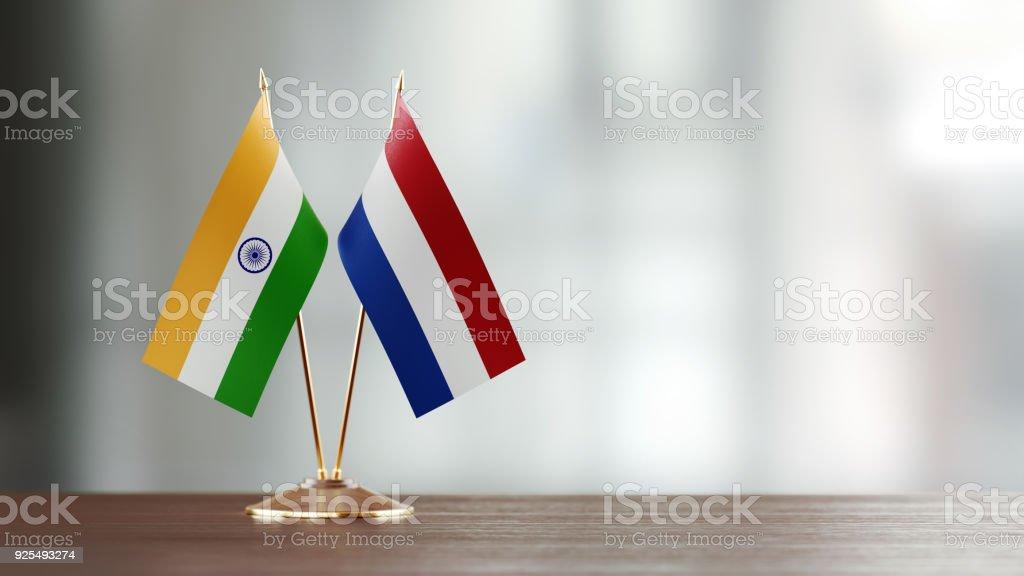 Par de la bandera India y los países bajos en un escritorio sobre fondo Defocused - foto de stock