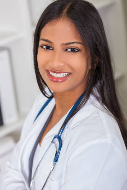 Indian Asian female medical doctor in a hospital office happy and smiling with stethoscope stock photo