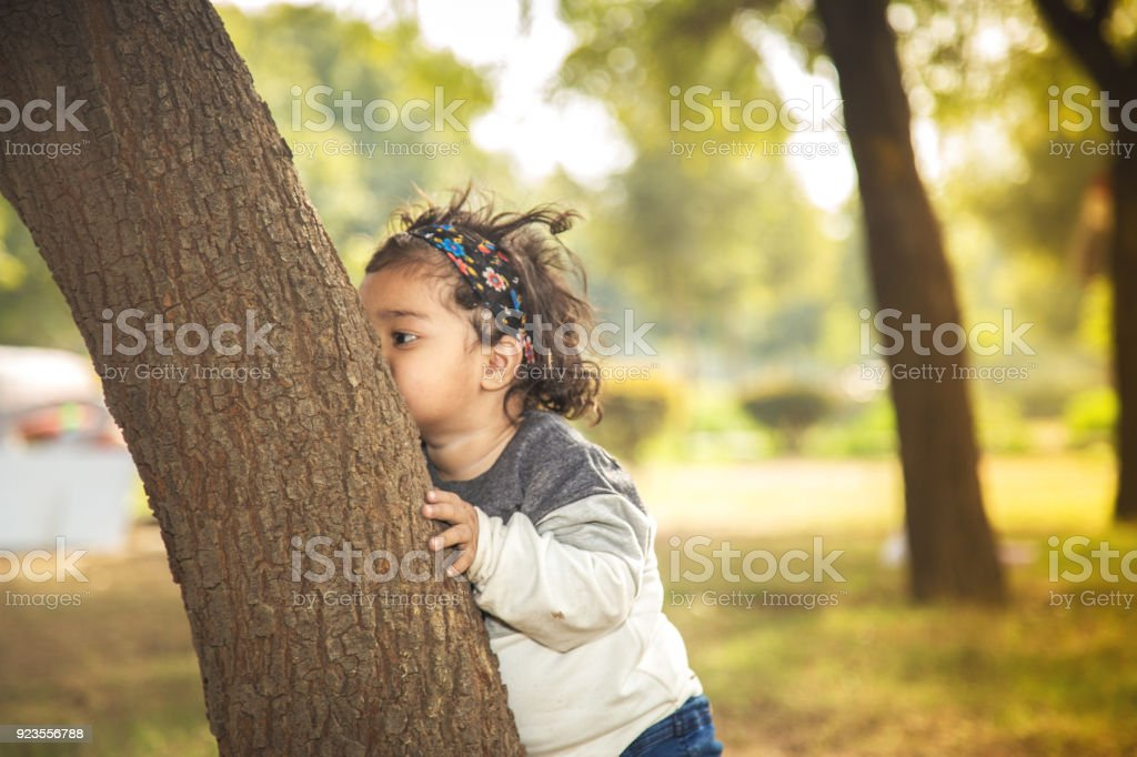 Indian Baby Girl Try To Hug Tree In Park Stock Photo - Download