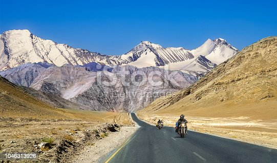 Indian tourists enjoy bike ride on national highway with scenic landscape at Ladakh India.
