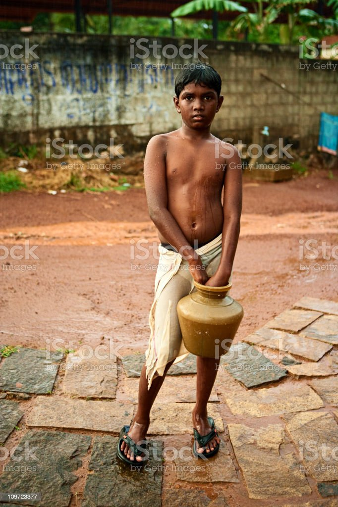 Indian boy standing in the pouring rain. royalty-free stock photo