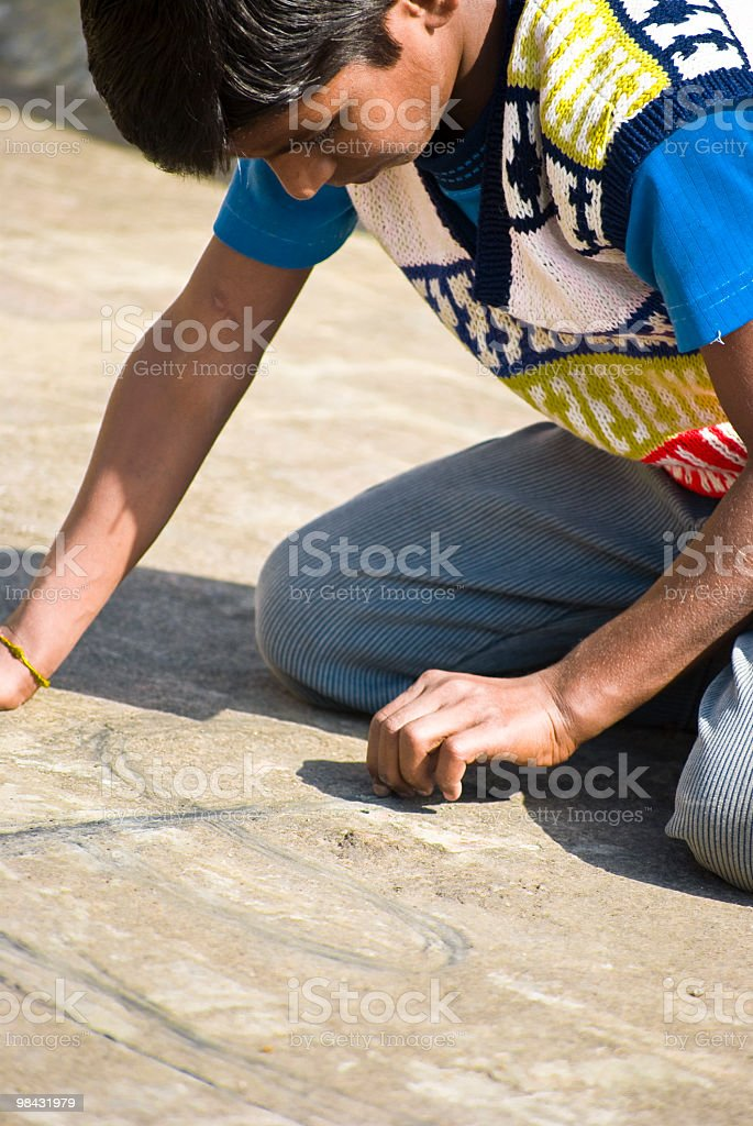 Indian boy writing on floor - India poverty royalty-free stock photo
