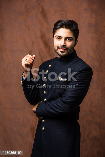 Indian bridegroom wears ethnic or traditional cloths,  Male fashion model with dark blue sherwani, posing / standing against brown grunge background, selective focus