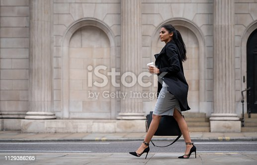 Beautiful Indian business woman walking on the street drinking a cup of coffee on the go