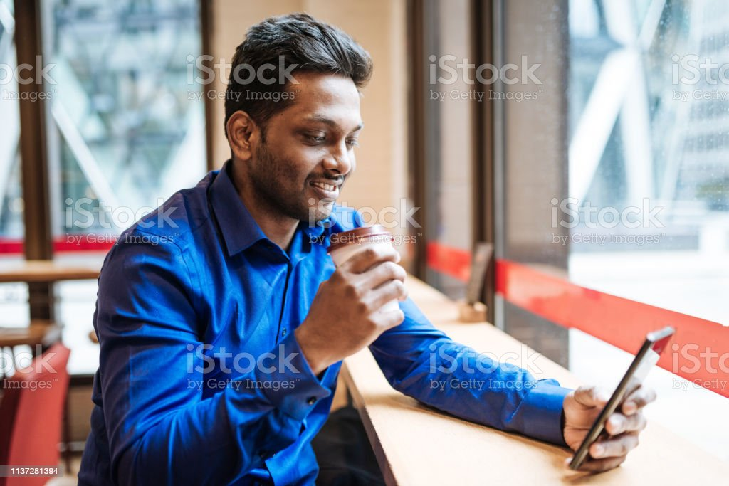 Indian Millennial man in London, UK, running his business and using...