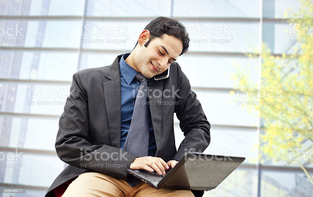 Indian Businessman on the phone and Using Laptop Office Building royalty-free stock photo