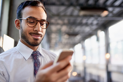 istock Indian businessman smiling confidently and surfing the net on a smartphone 660751378