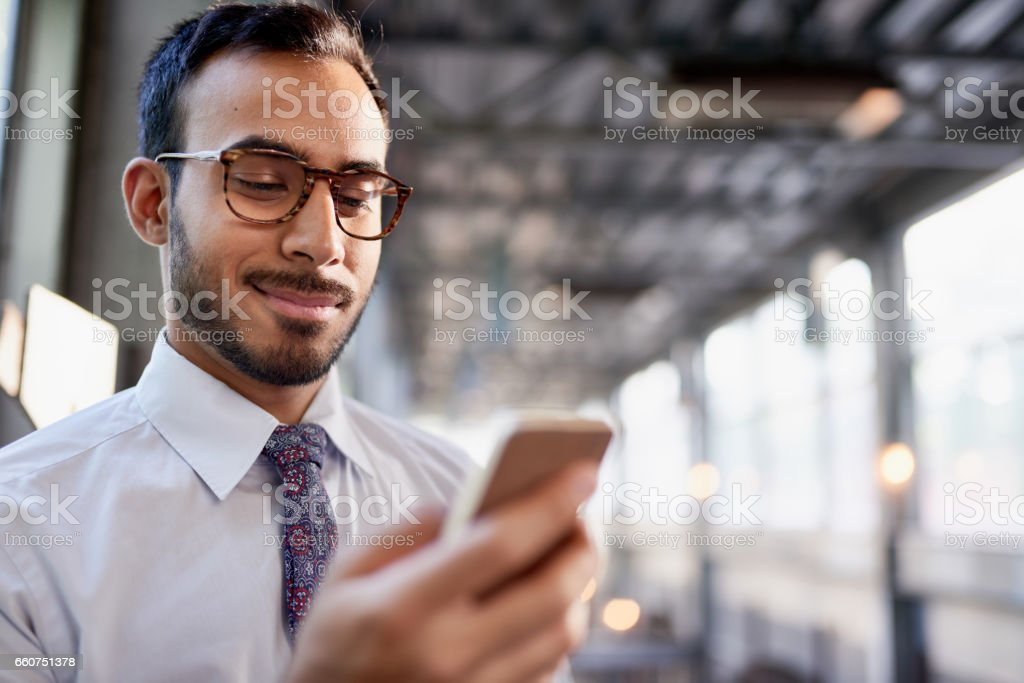 Indian businessman smiling confidently and surfing the net on a smartphone stock photo