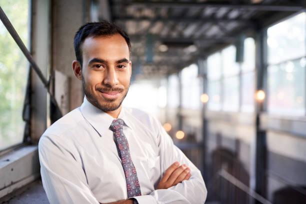 indischer geschäftsmann lächelt selbstbewusst mit stadtbild-hintergrund - indische kultur stock-fotos und bilder