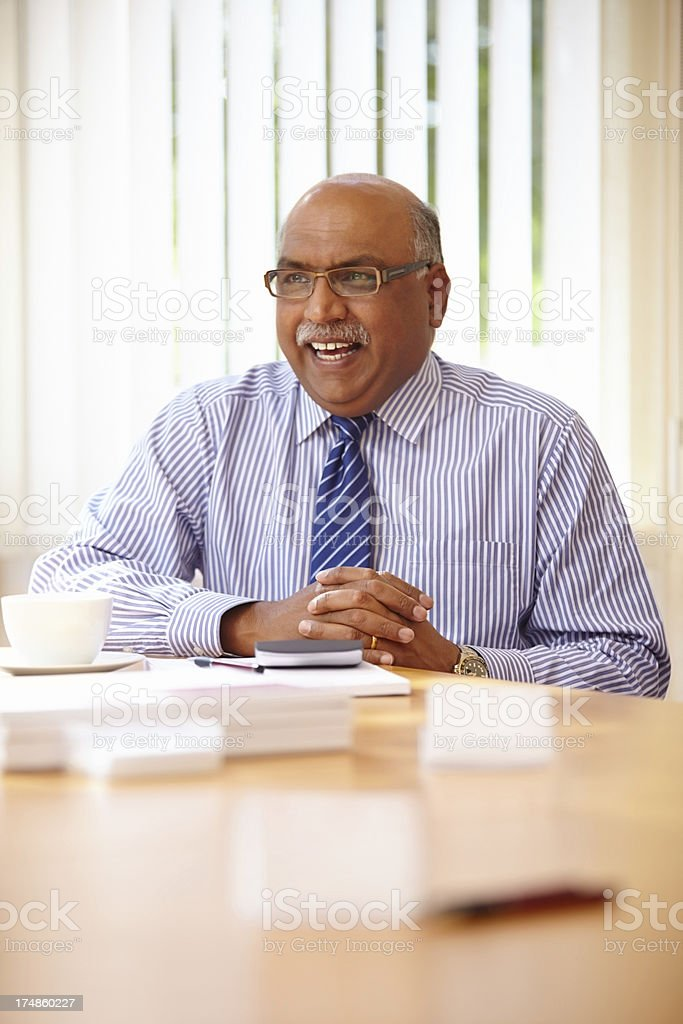 Indian businessman smiling in a meeting at office royalty-free stock photo