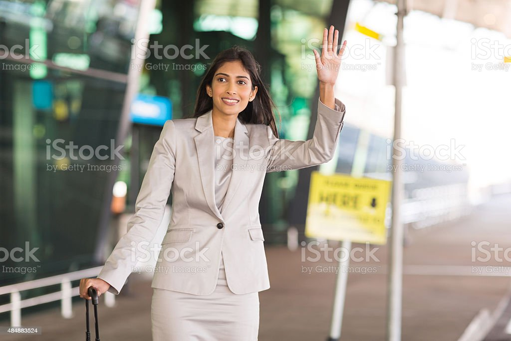 indian businesswoman hailing for a taxi stock photo