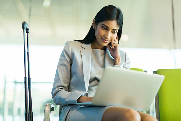 indian businesswoman using laptop computer at airport stock photo