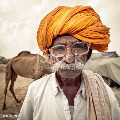 Portrait of an indian Camel Trading Merchant with vintage old glasses, white beard and typical orange turban at the Pushkar Camel Fair, Pushkar, Rajasthan, India. Portrait Series. Edited, Desaturated, Masked. Squared.