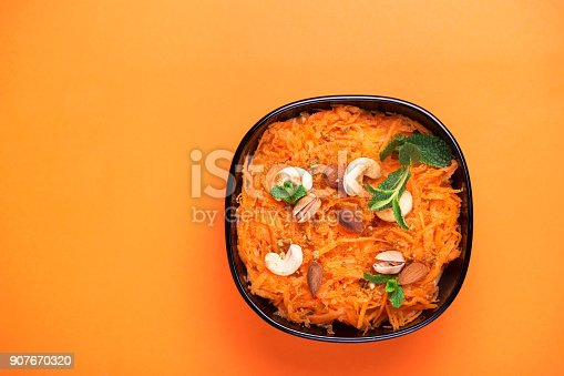 909460438 istock photo Indian carrot Gajar halwa. Copyspace, top view, flatlay. Color surge 907670320