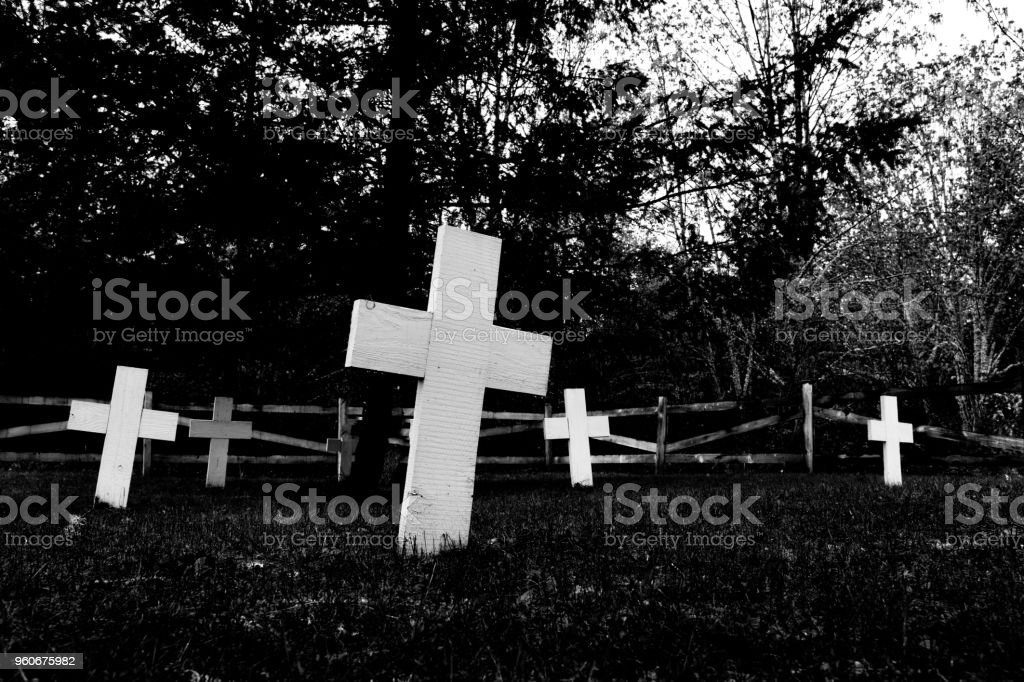 Indian cemetery abstract showing tilted white crosses and a dark spooky tree and fence stock photo