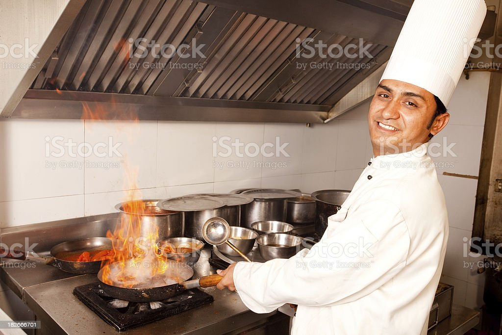 Indian Chef working cooking in a Restaurant Kitchen stock photo