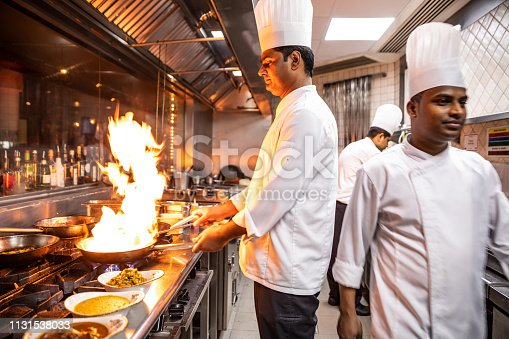 Indian chefs cooking in a professional kitchen of a gourmet restaurant.
