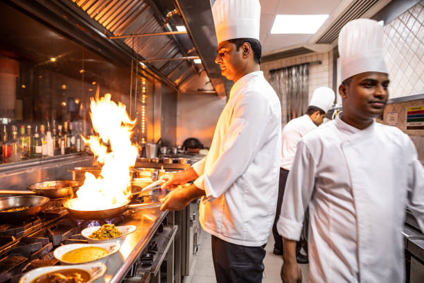 indian chefs cooking in a professional kitchen of a gourmet restaurant - busy restaurant kitchen stock pictures, royalty-free photos & images