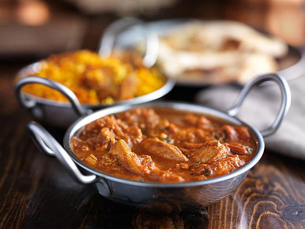 indian chicken curry meal indian butter chicken curry in balti dish with naan bread in background balti dish stock pictures, royalty-free photos & images