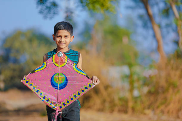 indian child playing with kite stock photo