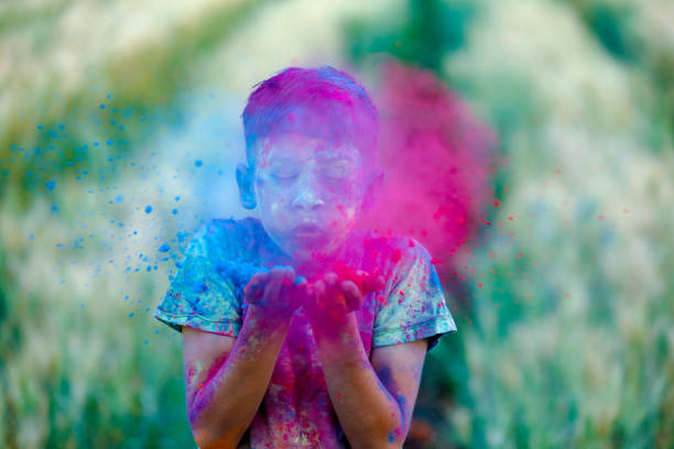 Indian child playing with the color in holi festival Indian child playing with the color in holi festival colored powder stock pictures, royalty-free photos & images