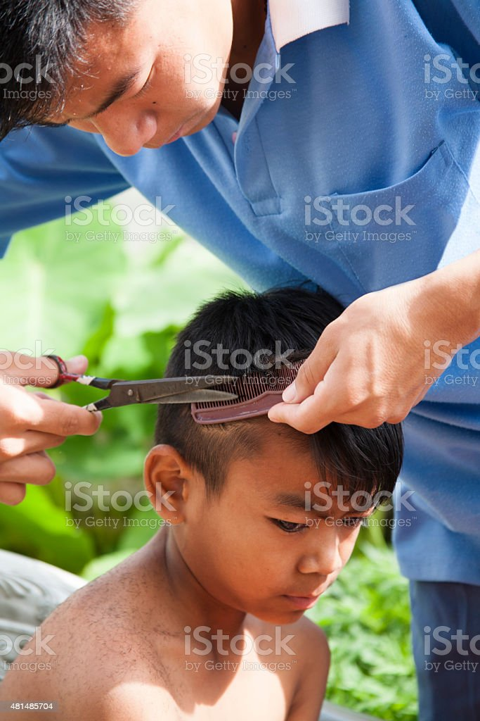 Indian children getting haircuts. Older boy cuts younger child's hair. stock photo