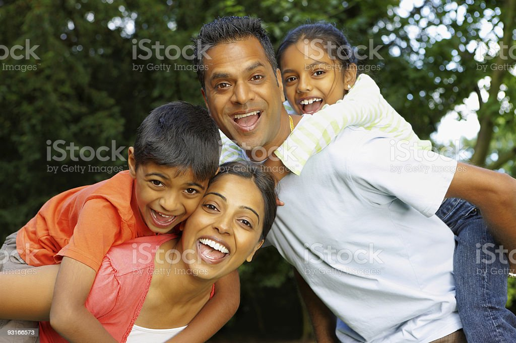 Indian children riding on their parents backs outdoors royalty-free stock photo