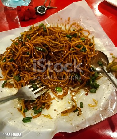A photo of Indian Chinese noodles meal with spoons.red color Chinese dish.