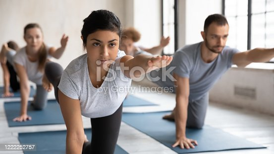 Serious focused Indian ethnicity female yoga instructor and group of young people performing Parsva Balasana Bird Dog Pose during workout at sport club studio. Strengthens core and low back exercise