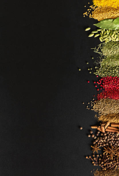 indian condiments on black table in high resolution. spices for cooking food on background of chalkboard with empty space. - spezia foto e immagini stock