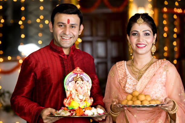 Indian couple carrying statue of Hindu god Ganesh and plate of sweet food stock photo