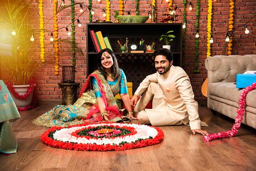 Indian couple making flower Rangoli on Diwali or Onam Festival, taking selfie or holding sweets